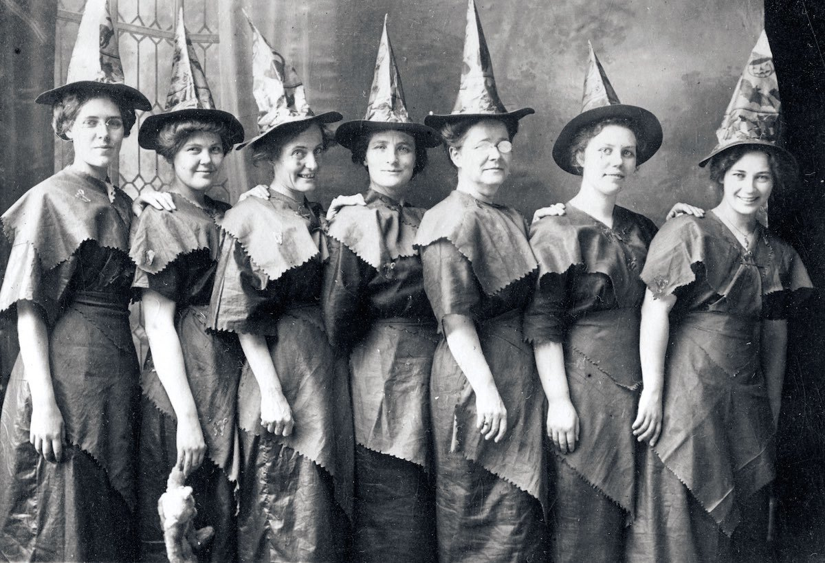 1617631584-content-c-1910-a-coven-of-witches-line-up-for-a-halloween-portrait-dressed-in-festive-hats-and-im.jpeg